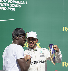 October 22, 2017 - Austin, Texas, U.S - 44 LEWIS HAMILTON driver for Mercedes AMG Petronas F1 Team celebrating 62nd Win with ''USAIN BIOLT'' 8 time Olympic gold medalist.  Being presenting with the signature Gold Shoes. (Credit Image: © Hoss Mcbain via ZUMA Wire)