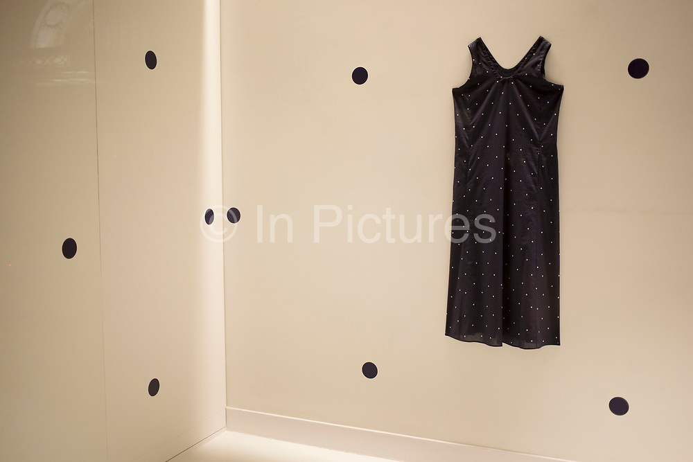 Black polka dot dress in a shop window display. London, UK. The minimal fashion design statement in the dress is echoed in the interior design.