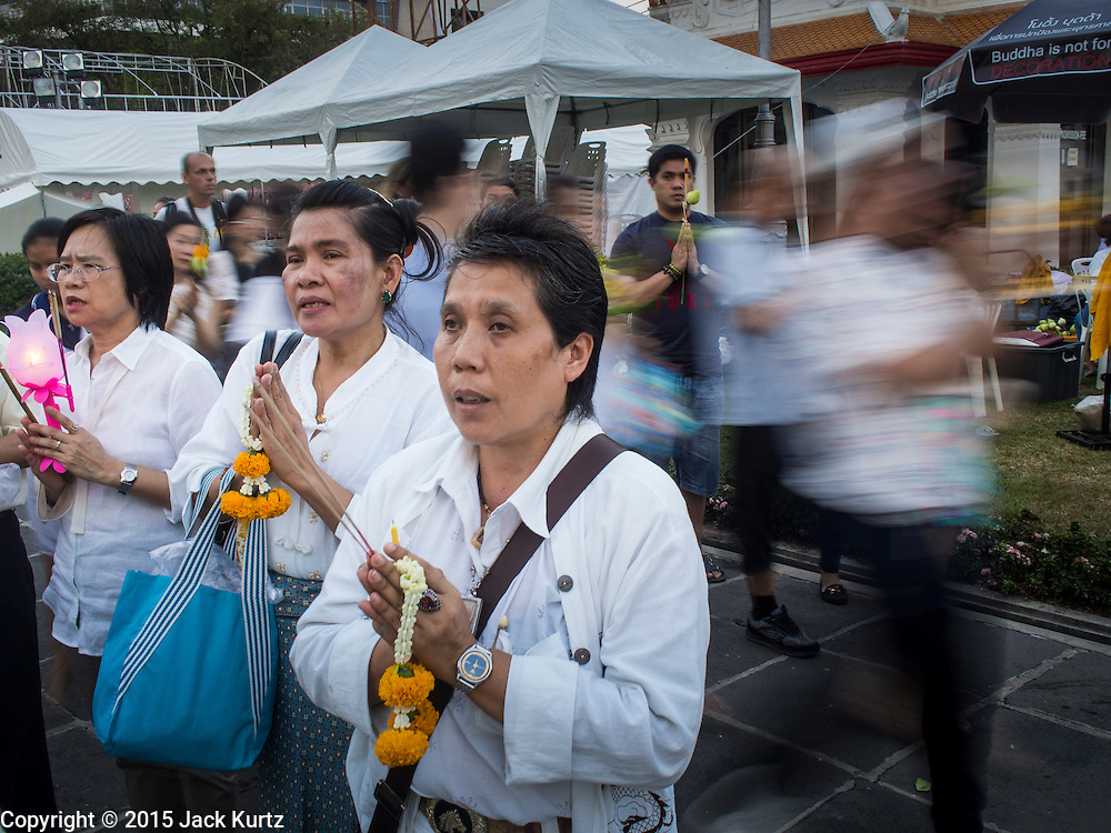 """04 MARCH 2015 - BANGKOK, THAILAND: People pray while others in a procession around the """"wiharn,"""" or prayer hall, pass them at Wat Benchamabophit on Makha Bucha Day. Makha Bucha Day is an important Buddhist holy day and public holiday in Thailand, Cambodia, Laos, and Myanmar. Many people go to temples to perform merit-making activities on Makha Bucha Day. Wat Benchamabophit is one of the most popular Buddhist temples in Bangkok.    PHOTO BY JACK KURTZ"""