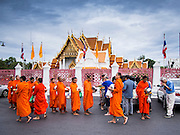 """21 JULY 2013 - BANGKOK, THAILAND:  A man gives monks at Wat Benchamabophit food and alms on the first day of Vassa, the three-month annual retreat observed by Theravada monks and nuns. On the first day of Vassa (or Buddhist Lent) many Buddhists visit their temples to """"make merit."""" During Vassa, monks and nuns remain inside monasteries and temple grounds, devoting their time to intensive meditation and study. Laypeople support the monastic sangha by bringing food, candles and other offerings to temples. Laypeople also often observe Vassa by giving up something, such as smoking or eating meat. For this reason, westerners sometimes call Vassa the """"Buddhist Lent.""""       PHOTO BY JACK KURTZ"""