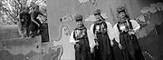 """Mädchen in traditioneller Düdinger Kränzlitracht mit Kopfschmuck. Die Kränzlitracht (Kränzli, im Dialekt """"ds Chränzli"""" = kleiner Kranz) ist die älteste und zugleich die bekannteste Sensler Tracht. Ihren Namen verdankt sie dem glitzernden Kränzli, welches aus Flitterli, Schlötterli, Pailleten, Schaum- und Glasperlen und Stoff-blümchen besteht.<br /> Sie wird aber auch Prozessions- oder """"Chrüzgangstracht"""" (= Kreuzgang, d.h. dem Kreuz folgend betend um die Pfarrkirche gehen) genannt, weil sie seit etwa der Mitte des 19. Jahr-hunderts zur kirchlichen Prozessions- und Kreuzgangstracht umgewandelt und somit, dank dem Eingreifen der Kirche, praktisch unverändert bis zum heutigen Tag erhalten geblieben ist. Ursprünglich war sie jedoch die festtägliche Volkstracht der Töchter.<br /> Die Kränzlitracht gehört zu den ältesten und farbigsten Trachten der Schweiz. Sie weist Elemente aus der Mode verschiedener Epochen auf. Gewisse Bestandteile reichen gar bis ins 17. Jahrhundert zurück.<br /> Die Kränzlitracht war ursprünglich überall im Sensebezirk verbreitet. Heute gibt es """"d'Chränzleni"""" als eigentliche Kreuzgangs- und Prozessionstracht nur noch in den Pfarreien Düdingen, Tafers und Heitenried. Bis in die 1960er Jahre hinein wurde die Kränzlitracht jeweils am ersten Sonntag des Monats sowie an grossen Marien- und Festtagen getragen. In Düdingen wird die Kränzlitracht am Herrgottstag und bei besonderen Festen getragen."""