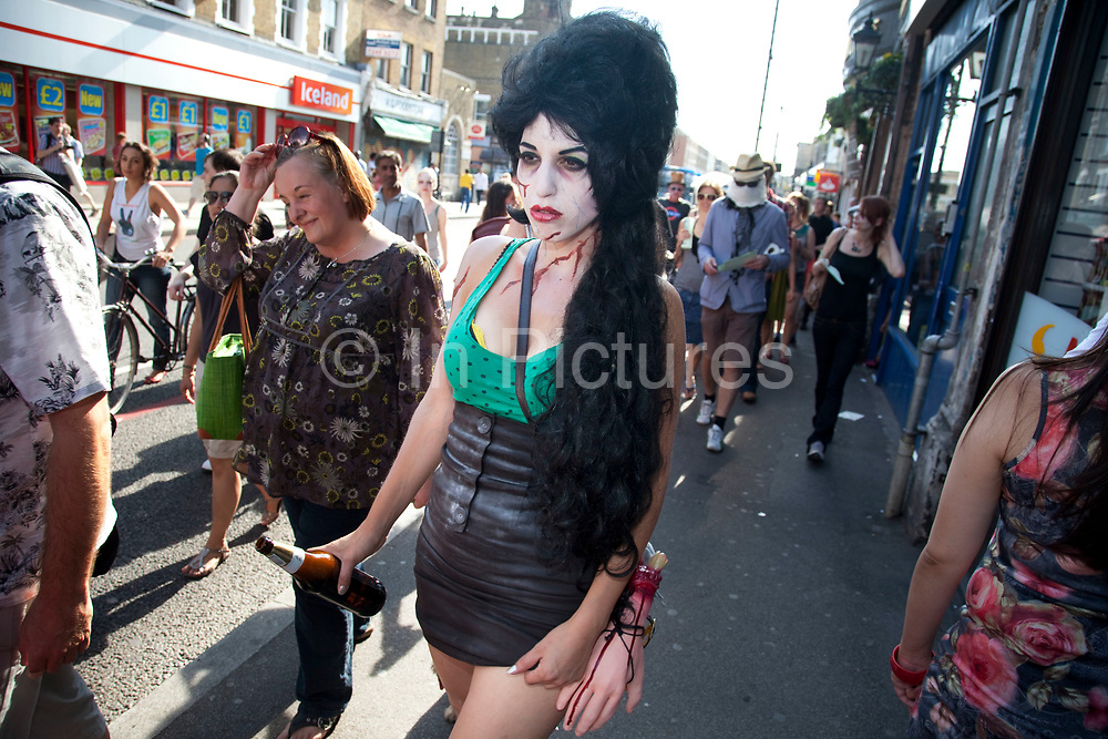 """Protester as an undead Amy Winehouse. Stoke Newington Zombie-a-thon. Hundreds of people joined together in protest in North London to demonstrate against the planned opening of a large Sainsbury's supermarket. Dressed up as zombies the protesters were making the point that they should keep local shops in the area and not have the high street ruined by large chains. The action by Stokey Local says: """"In Stoke Newington, even the dead are rising up to say 'no' to a proposed Sainsbury's development."""" Walking slowly as if in a zombie film the march culminated in passing a Sainsbury's Local supermarket on the High Street. In the middle of June it was announced that a development is being planned for Wilmer Place, just beside Abney Park Cemetery on the corner of Church Street and the High Street – right in the heart of Stoke Newington. The proposed development comprises a large Sainsbury's supermarket and 44 homes and has significant implications for thediversity of the local economy, local employment, transport & traffic, noise and safety and local heritage."""