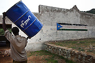 A man stores an oil barrel in the Nuba mountains where supplies are running low.