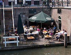 Busy outdoor summer cafe beside canal Oudegracht in central Utrecht in the Netherlands