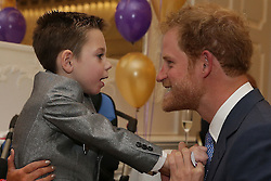 Prince Harry (right) reacts as he greets Inspirational Child Award Winner Ollie Carroll, as he attends the WellChild Awards in London. The awards recognise the courage of seriously ill children, their families and carers.
