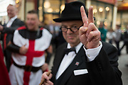 Winston Churchill impersonator, Derek Herbert gives a V for Victory after making the wartime leaders Battle of Britain speech in front of three knights and lunchtime drinkers on St Georges Day in Leadenhall Market in the capitals financial district aka The Square Mile, on 23rd April, City of London, England.