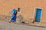 Traditional dressed woman walks with her child in front of an old clay house.
