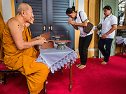 14 DECEMBER 2015 - BANGKOK, THAILAND:  People pick up mementoes of  the Supreme Patriarch before the start of his funeral at Wat Bowon Niwet in Bangkok. Somdet Phra Nyanasamvara, who headed Thailand's order of Buddhist monks for more than two decades and was known as the Supreme Patriarch, died Oct. 24, 2013, at a hospital in Bangkok. He was 100. He was ordained as a Buddhist monk in 1933 and appointed as the Supreme Patriarch in 1989. He was the spiritual advisor to Bhumibol Adulyadej, the King of Thailand when the King served as a monk in 1956. His funeral, which will take three days,   Dec. 15-17, will be attended by thousands of Thais and most of the Royal Family. Buddhist clergy from around the world are expected to attend.      PHOTO BY JACK KURTZ