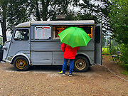 Waiting in the rain with a green umbrella at the pizza take away, Charmes sur l'Herbasse, France.
