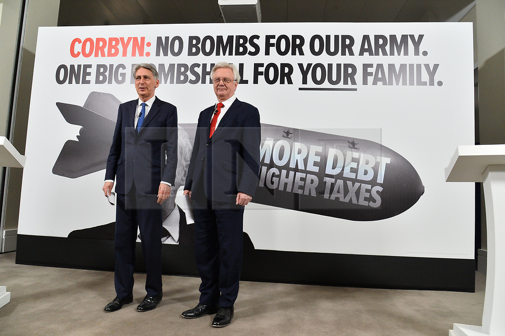 """© Licensed to London News Pictures. 03/05/2017. London, UK. Chancellor of the Exchequer PHILLIP HAMMOND and DAVID DAVIES Secretary of State for Exiting the European Union speak at a General Election Campaign event featuring a poster of Labour party leader JEREMY CORBYN with the slogan """"More debt, higher tax."""" Photo credit: Ray Tang/LNP"""