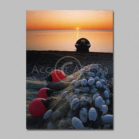 Alaska.Kotzebue. Sunset over the Chukchi Sea warms a fishing boat and gill net.