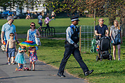 A Police PCSO patrols the common giving out low key advice on the Stay at Home guidance to the few people who are sitting and not exercising, most leave - Clapham Common is pretty quiet now Lambeth Council has taped up all the benches, put up signs and organised patrols by wardens. The 'lockdown' continues for the Coronavirus (Covid 19) outbreak in London.
