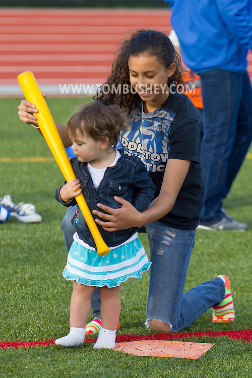 Middletown, New York - A Middletown High School athlete helps a toddler with a baseball bat while playing gamesat Faller Stadium during Family Fun Night on May 17, 2013.
