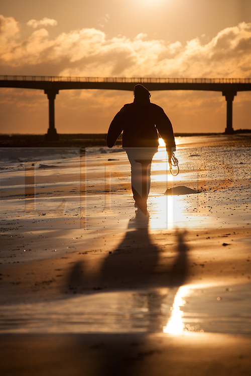 © Licensed to London News Pictures. 27/12/2014. Bembridge, Isle of Wight, UK. A dog walker takes stroll at sunrise on Lane End Beach on the Isle of Wight this morning, 27th December 2014. The South of England is expected to experience clear skies with a strong wind for the weekend. Photo credit : Rob Arnold/LNP