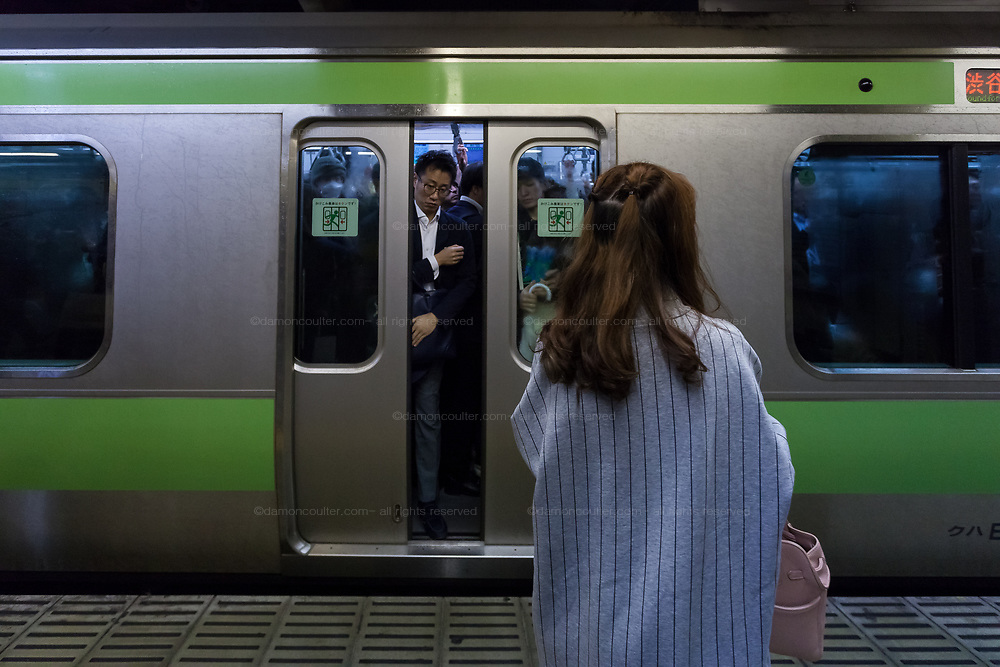 A salaryman or make office worker watches a woman alone on the platform as the doors on a Yamanote Libe train close. Shinjuku Station Shinjuku, Tokyo, Japan. Friday October 6th 2017