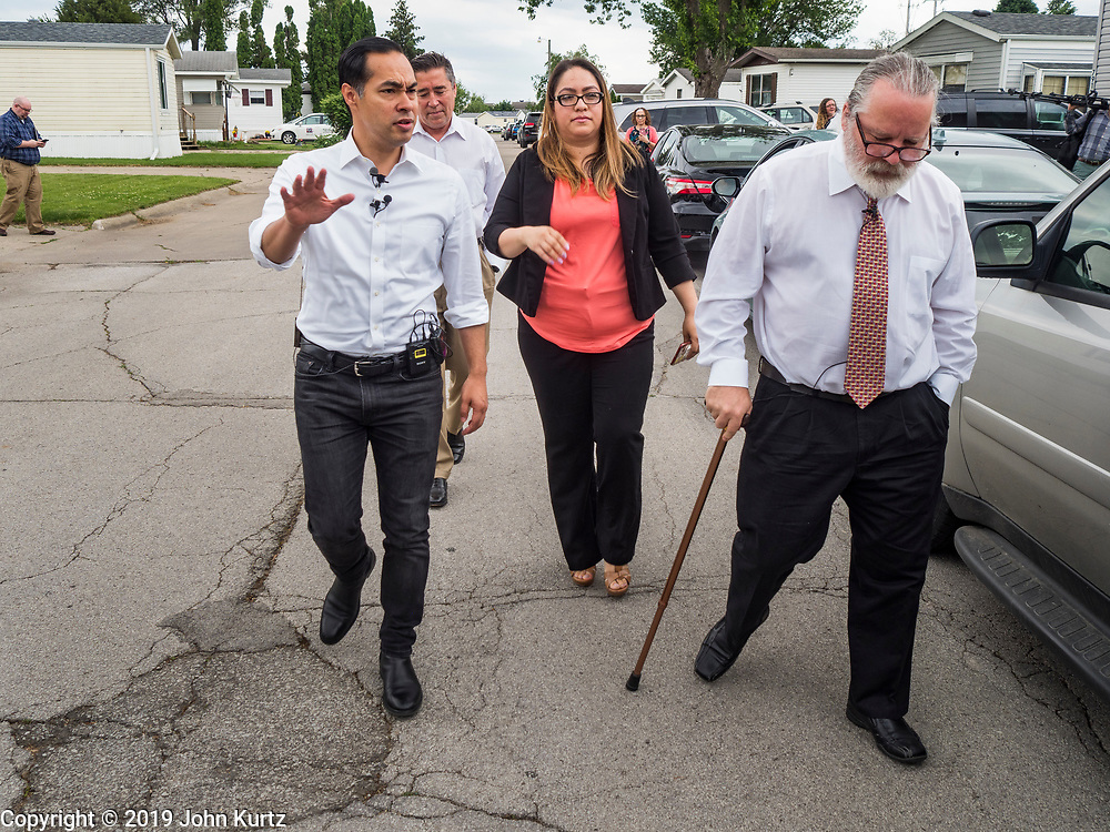 14 JUNE 2019 - WAUKEE, IOWA: JULIÁN CASTRO, left, Democratic presidential candidate and former Secretary of Housing and Urban Development during the Obama administration, follows DANIELA FRANCO, center, and MATT CHAPMAN, residents of Midwest County Estates, during a tour of the mobile home community in Waukee, a suburb of Des Moines, Friday. Castro met with residents of the community to talk about affordable housing. Mobile County Estates was sold in March and the new owners are trying to hike rents for lots in the community by 69%, an amount residents say they can't afford. Chapman is organizing opposition to the rent hike. Castro is visiting Iowa to support his candidacy for the Democratic ticket of the US Presidency. Iowa traditionally hosts the the first selection event of the presidential election cycle. The Iowa Caucuses will be on Feb. 3, 2020.                                  PHOTO BY JACK KURTZ