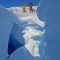 Mountaineers Tom Day and Mike Farny peer into a crevasse on the Calley Glacier on the Antarctic Peninsula, Antarctica.