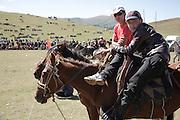 Young men watching a horseback wrestling competition, a popular Kyrgyz sport. Bosogo jailoo, Naryn province, Kyrgyzstan.