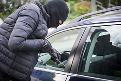 Thief breaking into a car using screwdriver