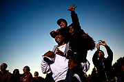 """Shaun Northern, of Chicago, holds on to his children, Shaun Northern Jr., 3, and Makayla Northern, 6, during the Democratic rally at Midway Plaisance in Hyde Park on Saturday October 30,  2010. """"It's a part of history what's going on here today,"""" said Northern."""