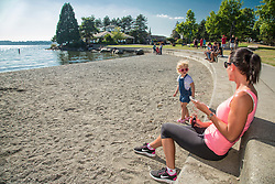 United States, Washington, Kirkland. Mother and daughter enjoy sandy beach on the waterfront on Lake Washington. MR