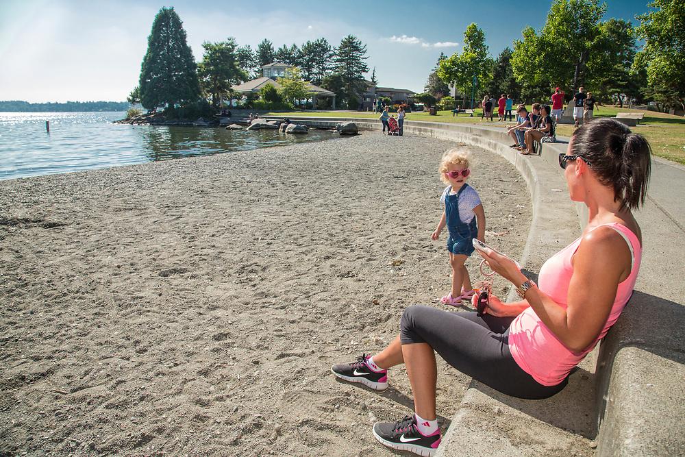 United States, Washington, Kirkland. Mother and daughter enjoy sandy beach on the waterfront on Lake Washington. MR