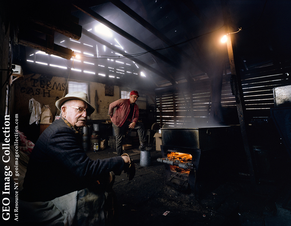 Interior of a sugar shack while maple sap is boiled to create maple syrup in Pittsfield, Vermont. The heat processing and boiling produces water vapor fog and reduces the light sap to heavy syrup used as a sweet condiment. The fog escapes through the porous clapboard walls. Collecting sap and boiling syrup are traditional spring activities in Yankee New England. Man on left is Charlie Colton and young man is Ray Colton. This shack is 150 years old and the heat is from a wood stove converted to gas.