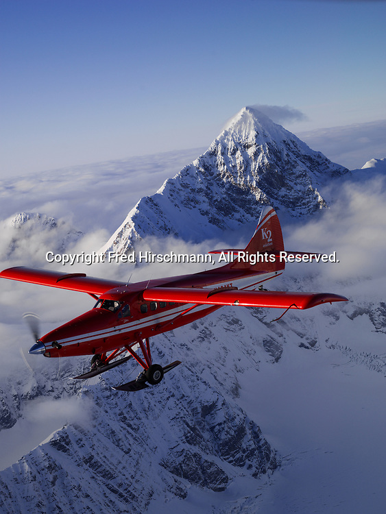 K2 Aviation's Turbo Otter on wheel skis flying past Mount Russell in Denali National Park, Alaska.