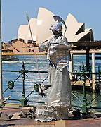"""A Sydney street artist dresses like Ares, ancient Greek god of war, with silver helmet, spear, shield, and gown. Sydney Opera House was opened in 1973 on Bennelong Point in Sydney Harbour, Sydney, New South Wales (NSW), Australia. It was conceived and largely built by Danish architect Jørn Utzon after a long gestation starting with his competition-winning design in 1957. Utzon received the Pritzker Prize, architecture's highest honor, in 2003: """"There is no doubt that the Sydney Opera House is his masterpiece… one of the great iconic buildings of the 20th century, an image of great beauty that has become known throughout the world – a symbol for not only a city, but a whole country and continent."""" The Sydney Opera House was honored as a UNESCO World Heritage Site in 2007."""