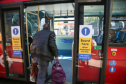 © Licensed to London News Pictures. 20/04/2020. London, UK. Passenger uses the middle-door for boarding a London bus. Transport for London has introduced middle-door boarding during the coronavirus outbreak and to slow the spread of COVID-19. The passengers are no longer able to pay their fare using the Oyster/contactless card reader which are next to the driver's seat. Photo credit: Dinendra Haria/LNP