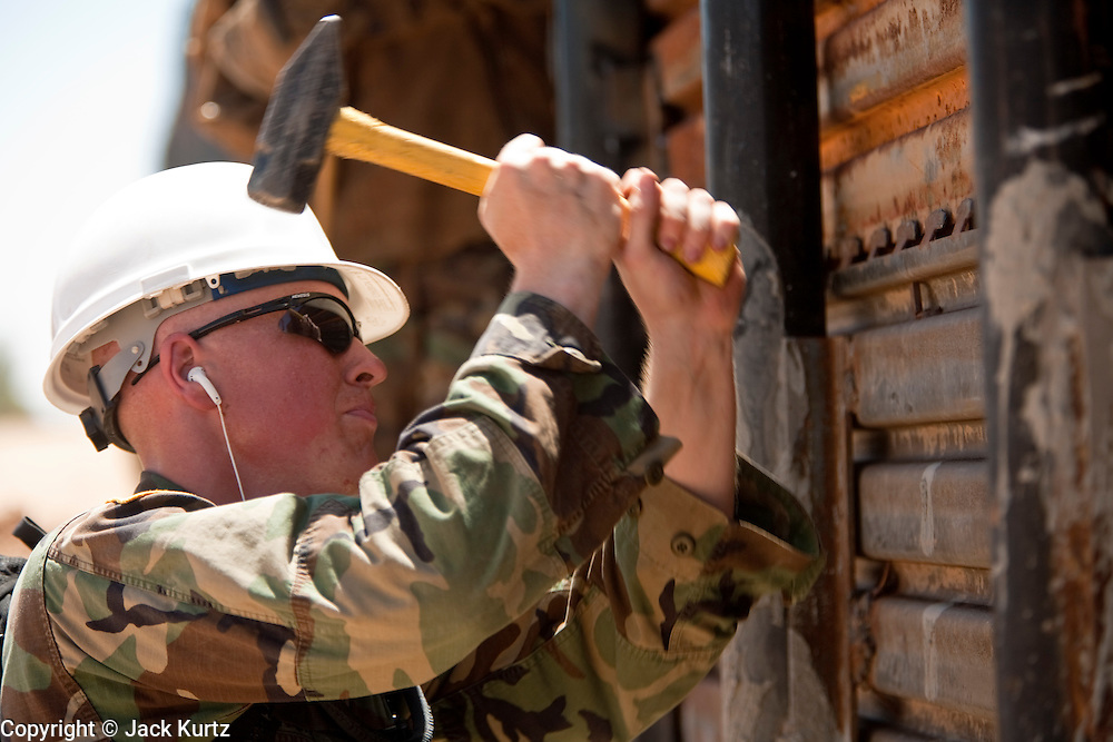 12 JUNE 2006 - SAN LUIS, AZ: Spc. Jesse Stone, from the Utah Army National Guard, works on a fence near San Luis, AZ. Fifty five members of the 116th Engineer Company, Combat Support Engineers, of the Utah Army National Guard are in San Luis, AZ, to build a fence and improve roads east of the San Luis Port of Entry on the US/Mexico border. The unit is the first of an estimated 6,000 US military personnel, almost all of them Army National Guard, who will be dispatched to the US/Mexico border by President Bush to help control immigration on the border. The Guardsmen will primarily build roads and fence and staff surveillance centers. They will not be engaged in first line law enforcement work.  Photo by Jack Kurtz