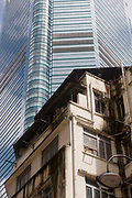 Old and new Hong Kong. A shimmering skyscraper rises above a residentail house in Hong Kong's Central district. Hong Kong is a mixture of new and old, rich and poor, new business versus tradition, wealth and westernisation towering over the traditional.
