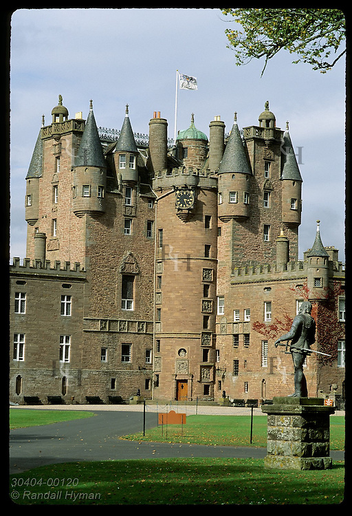Glamis Castle, childhood home of the Queen Mother, framed by Arnold Quellin's statue (1686) of King Charles I;  Glamis, Scotland.