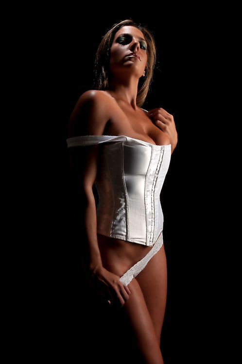 Young hispanic woman posing in white lingerie in dim light.