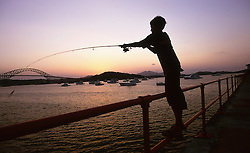 Silhouette of boy fishing in Bahia de Panama (Panama Bay) at sunset with fishing boats and bridge in background.