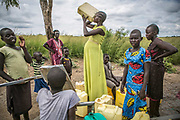 Seventeen-year-old Nyabuol Tut, center, quenches her thirst from a water pump as other women lined up their containers inside Bidibidi refugee settlement in northern Uganda. Nyabuol was gang-raped by Dinka soldiers twice, both in December 2015 and March 2017. She gave birth to Nyalit from the first rape by four soldiers and is eight months pregnant from the second rape by seven armed Dinka men. Her parents were shot to death by Dinka soldiers in between both conflicts in 2013 and 2016.