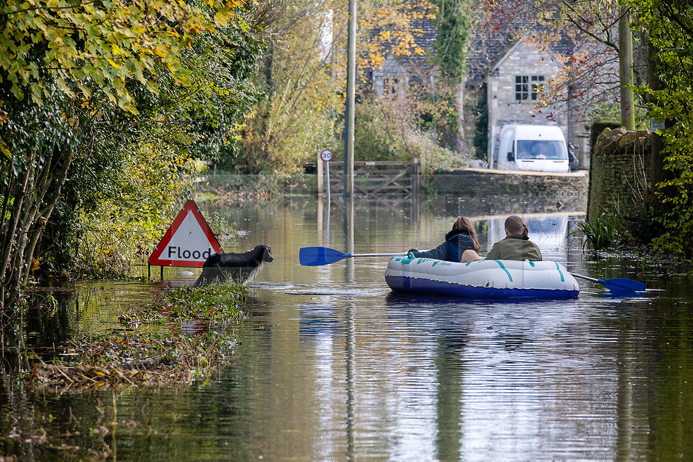 © Licensed to London News Pictures 16/11/2019, Cerney Wick, UK. Residents of Cerney Wick, near Cirecenster paddle down a flodded road in the village in a blow up dinghy. Photo Credit : Stephen Shepherd/LNP