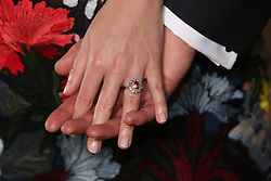 Princess Eugenie wears a ring containing a padparadscha sapphire surrounded by diamonds as she poses with Jack Brooksbank in the Picture Gallery at Buckingham Palace in London after they announced their engagement.