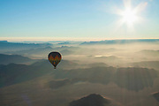 Overhead view of a hot air balloon in flight with mountains in the background in the Namib-Naukluft National Park, Namibia.
