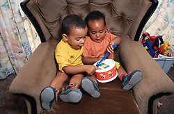 Two young brothers sitting in arm chair playing with toy drum,