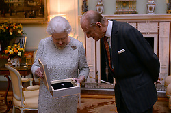 Queen Elizabeth II and the Duke of Edinburgh, look at the Federation Equestre Internationale (FEI) lifetime achievement award for her devotion to equestrian sport, presented to her by Princess Haya of Jordan and Keith Taylor, President of the British National Equestrian Federation, at Buckingham Palace, London.