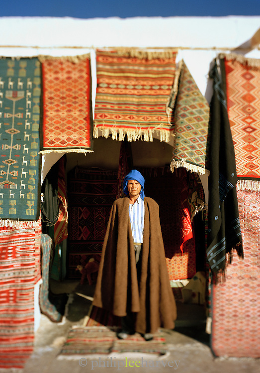 A man who sells carpets and rugs stands outside his shop in Tunisia