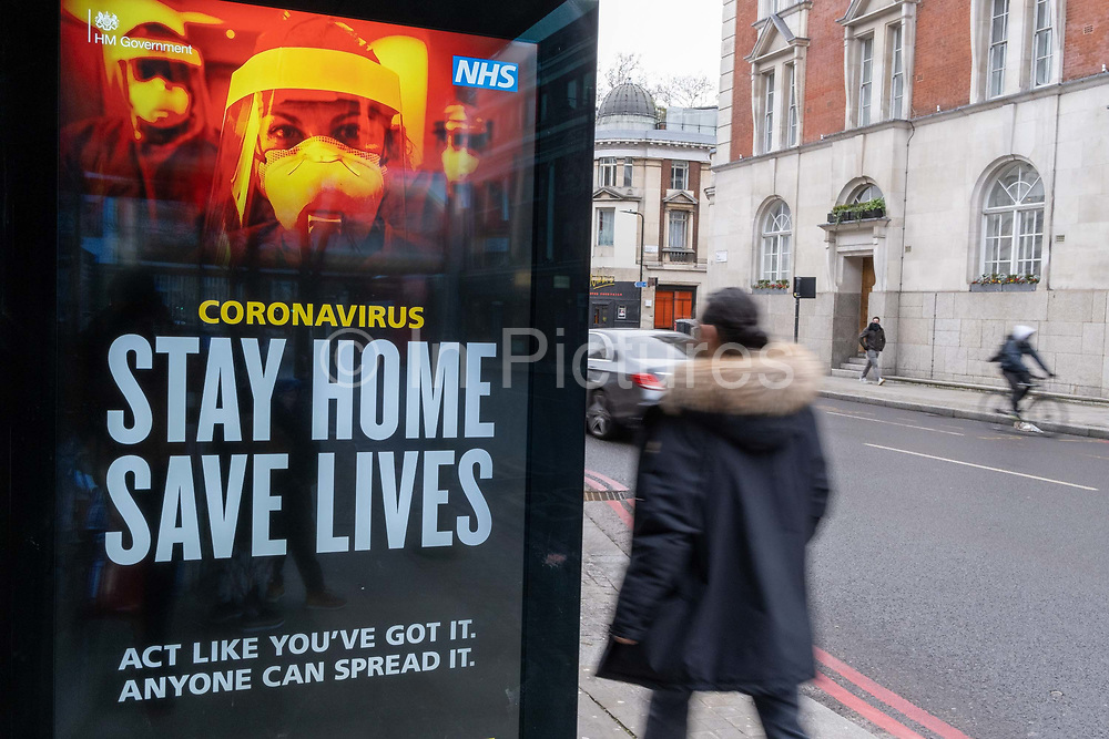 As the UK government tells the nation to prepare for the worst two weeks of the Coronavirus pandemic, a warning aimed at the population to stay at home and minimise contact with others, but in the week when new vaccination centres are opening, a Stay At Home message is displayed at a bus shelter in Shoreditch, on 11th January 2021, in London, England.