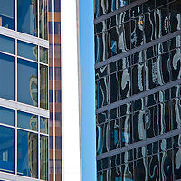 The sky is embraced in this image. The sky lends depth to the building on the right when one can see the sky through the windows and the reflections. Three buildings create a vortex for a slice of sky. The sky lends color to building on the left foreground.