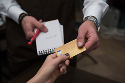 Man holding note pad and pen while accepting credit card payment from woman