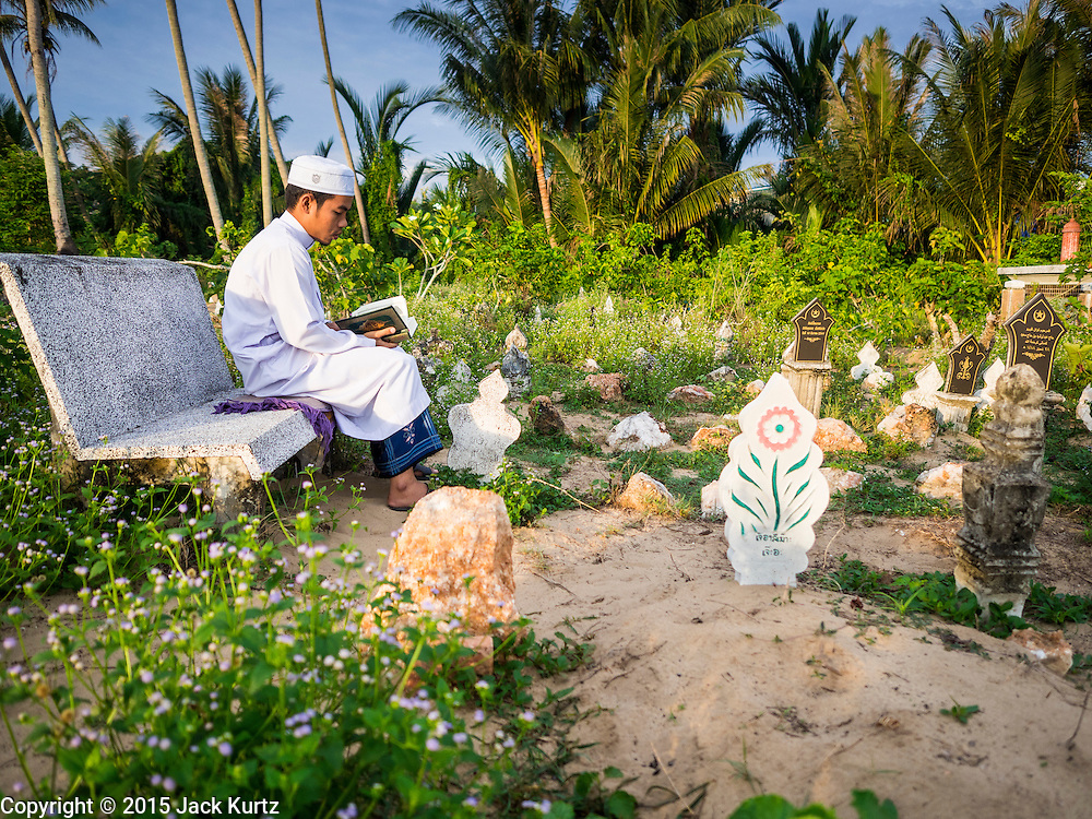 19 JUNE 2015 - PATTANI, PATTANI, THAILAND: A teenager prays in the Perkuboran To'Ayah, the Muslim cemetery in Pattani. It is more than 150 years old. The last Sultan of Pattani, who ruled until Siam (Thailand) annexed Pattani is buried in the cemetery. Many victims of political and sectarian violence that has wracked Thailand's three Muslim majority provinces, Pattani, Narathiwat and Yala are also buried in the cemetery. On Fridays, after morning prayers, Muslim men come to the cemetery to tend to the graves of their family members.   PHOTO BY JACK KURTZ
