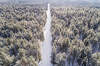 Aerial view of a road covered with snow in the forest of Naage in Estonia.