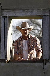 cowboy standing by a wooden framed window