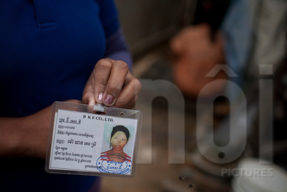A female worker presents her ID Card in a construction area, Phnom Penh, Cambodia, Southeast Asia