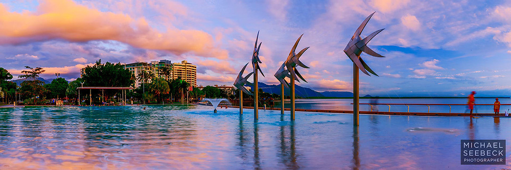 A panoramic photograph of the Cairns Esplanade Pool and Fish Sculptures at sunrise.<br /> <br /> Open Edition print